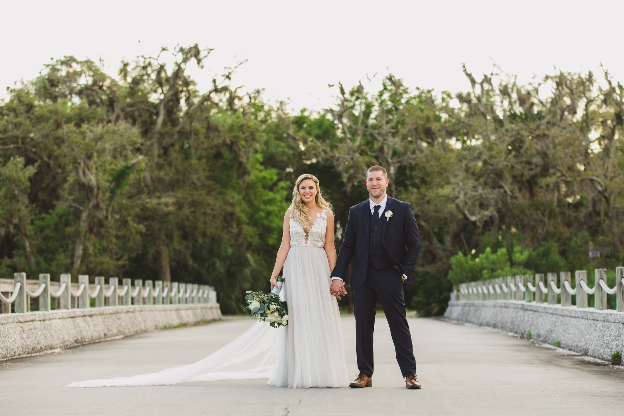 bride and groom standing in middle of road on bridge