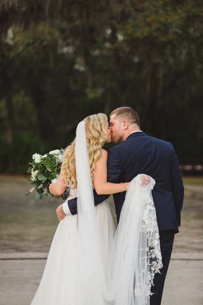 bride and groom kissing while walking