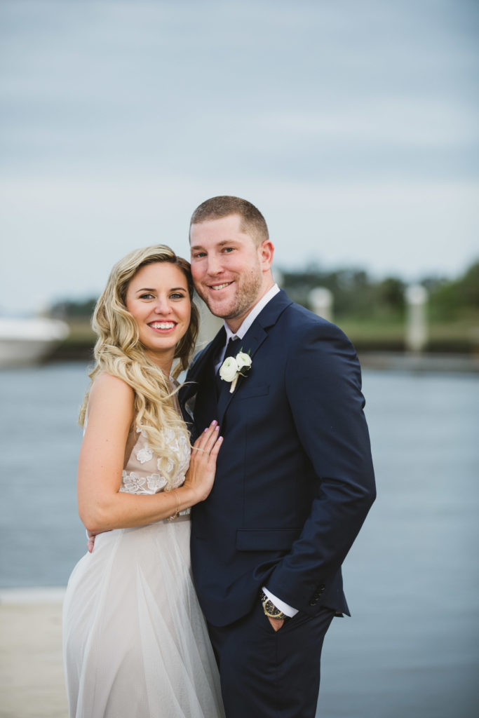 bride and groom standing on docks of obyc