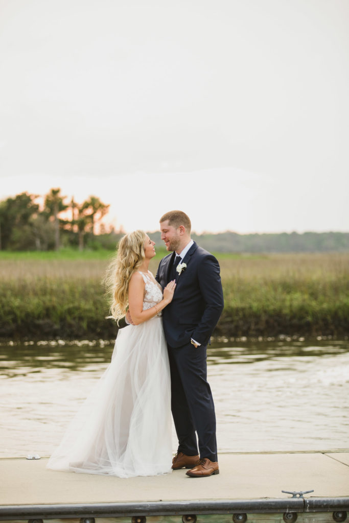 bride and groom on docks with water and marsh in background