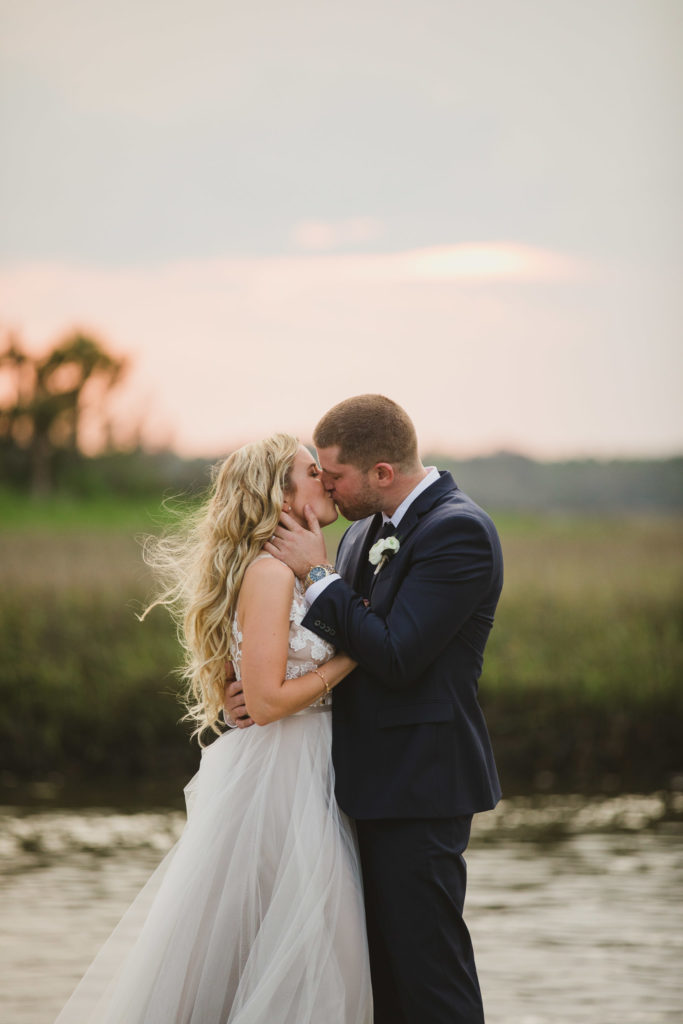 bride and groom kissing with river and sunset behind them
