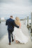groom and bride walking away on dock