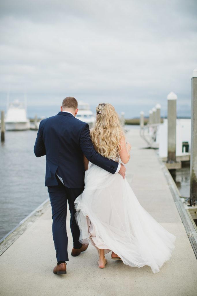groom and bride walking away on dock