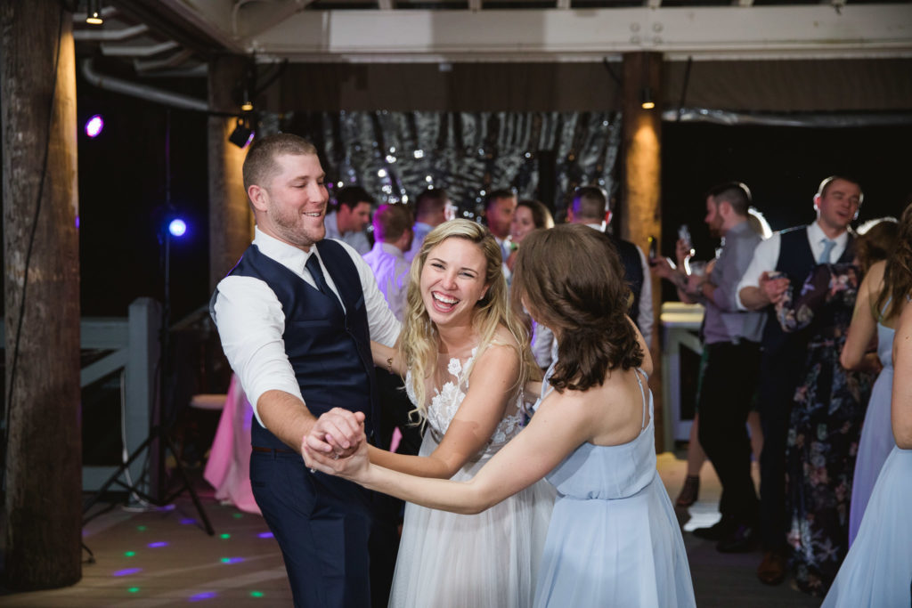 bride and groom and bridesmaid laughing and dancing