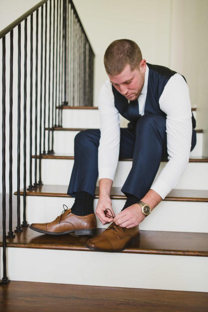groom tying shoe in stairs
