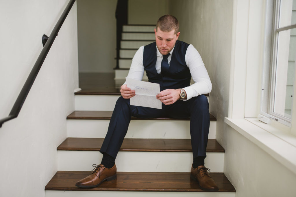 groom reading letter from bride while sitting in stairs