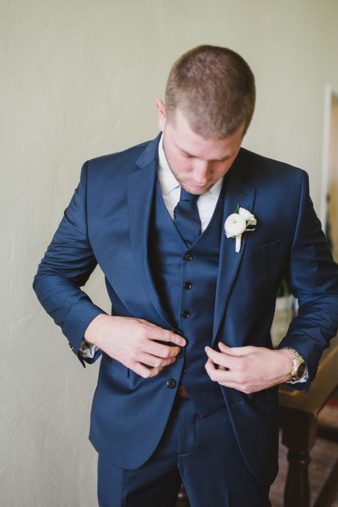 groom buttoning up his jacket getting dressed