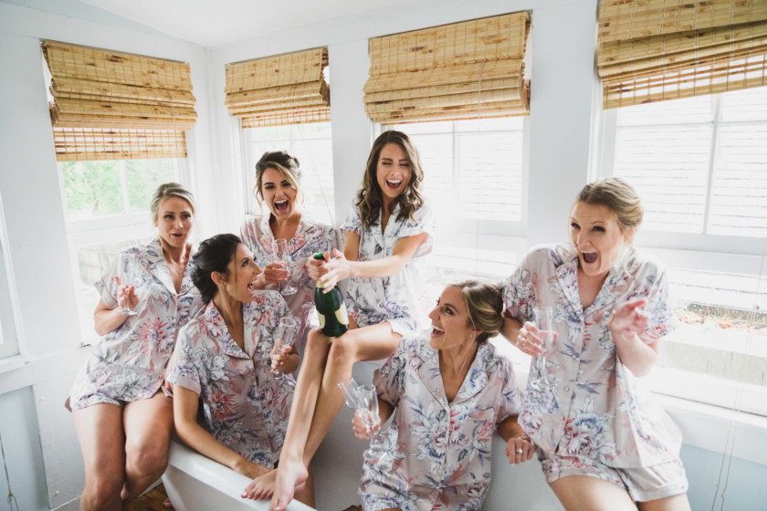 bride opening champagne bottle with bridesmaids in tub