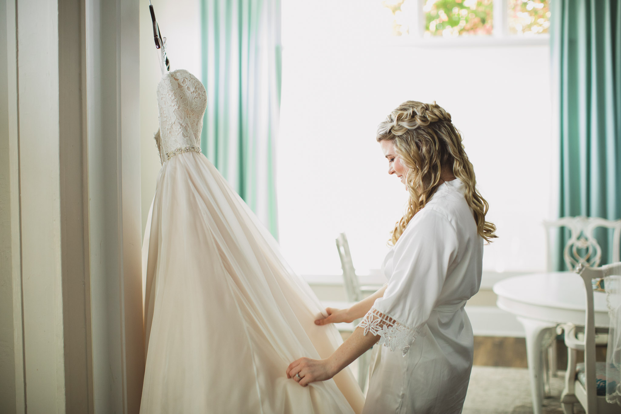 bride in bathrobe looking at her wedding gown in bridal suite at whit room