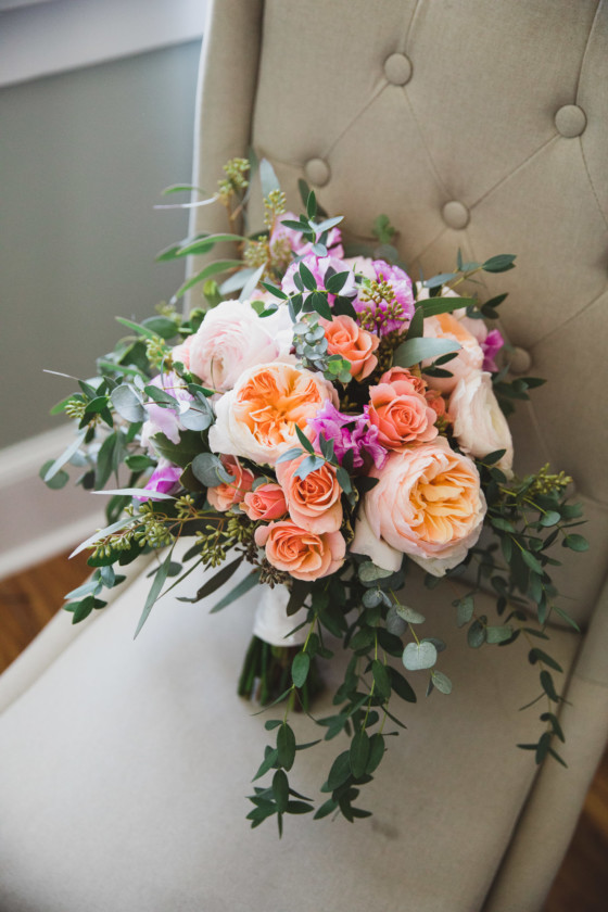 pink, orange, peach bride bouquet sitting on fabric chair