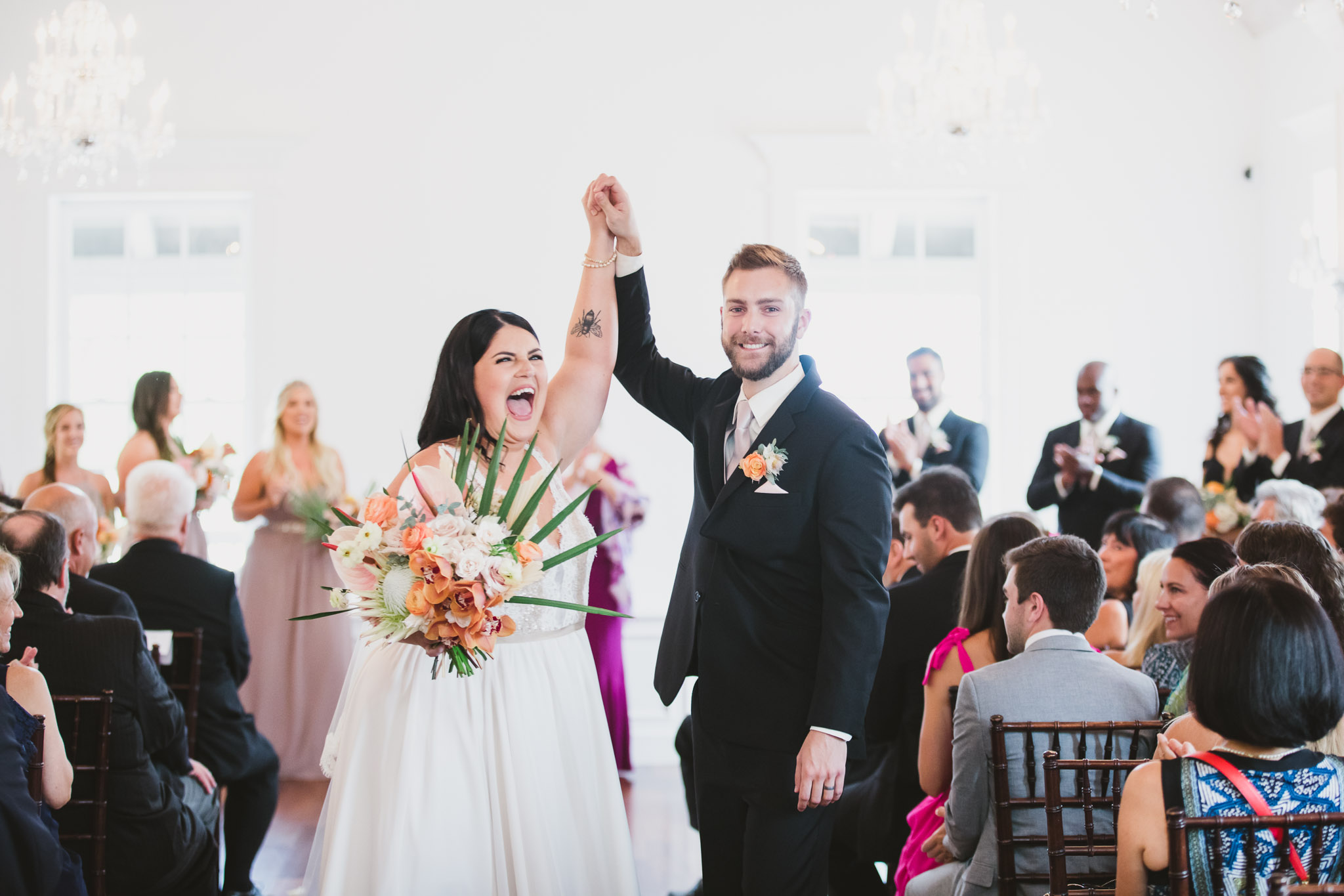 bride and groom high five each other walking down the aisle after ceremony at villa blanca