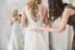 bridesmaid putting train on wedding gown