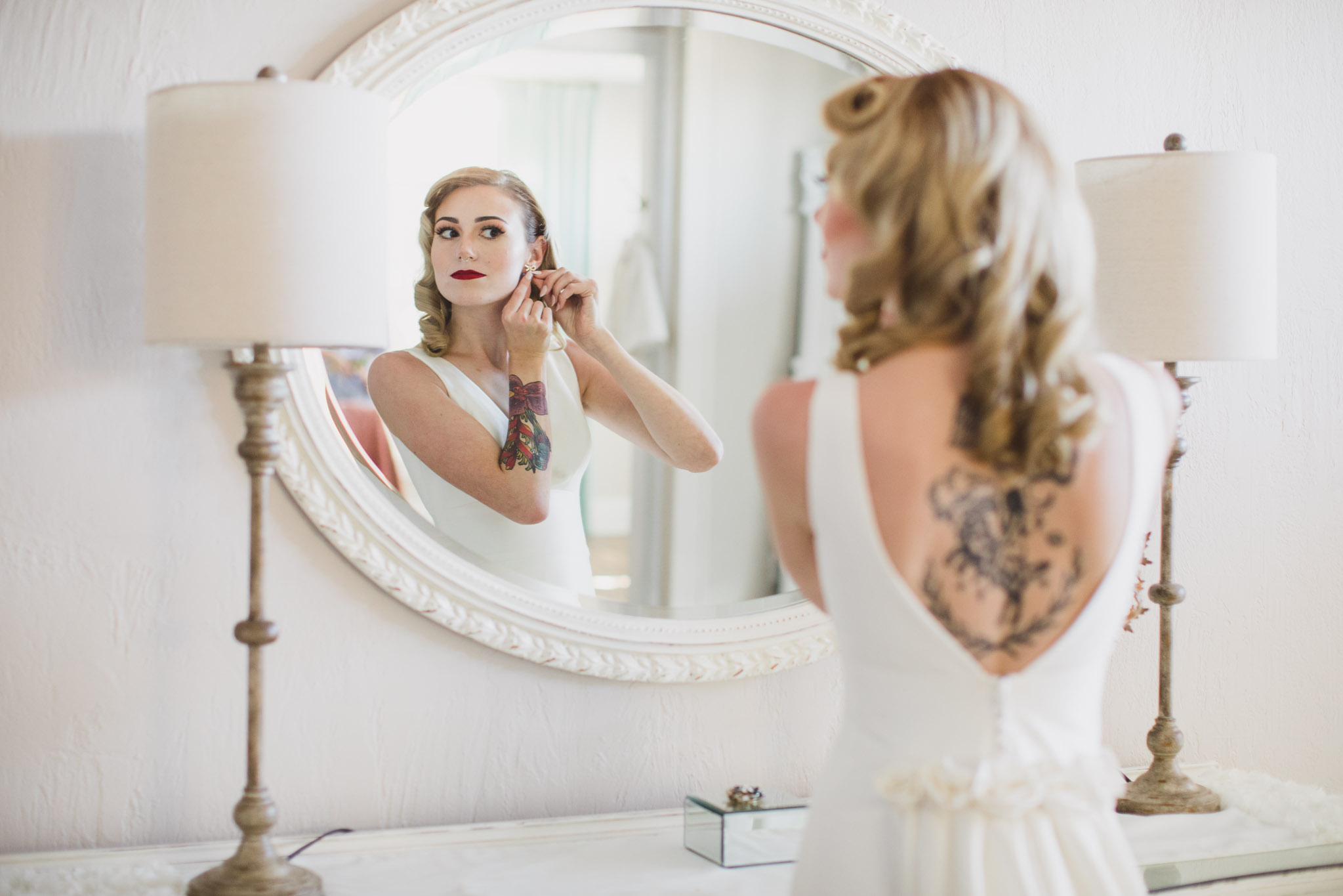 bride looking at herself in the mirror to put on earrings