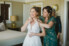bride getting help from her mom to put on necklace on wedding day