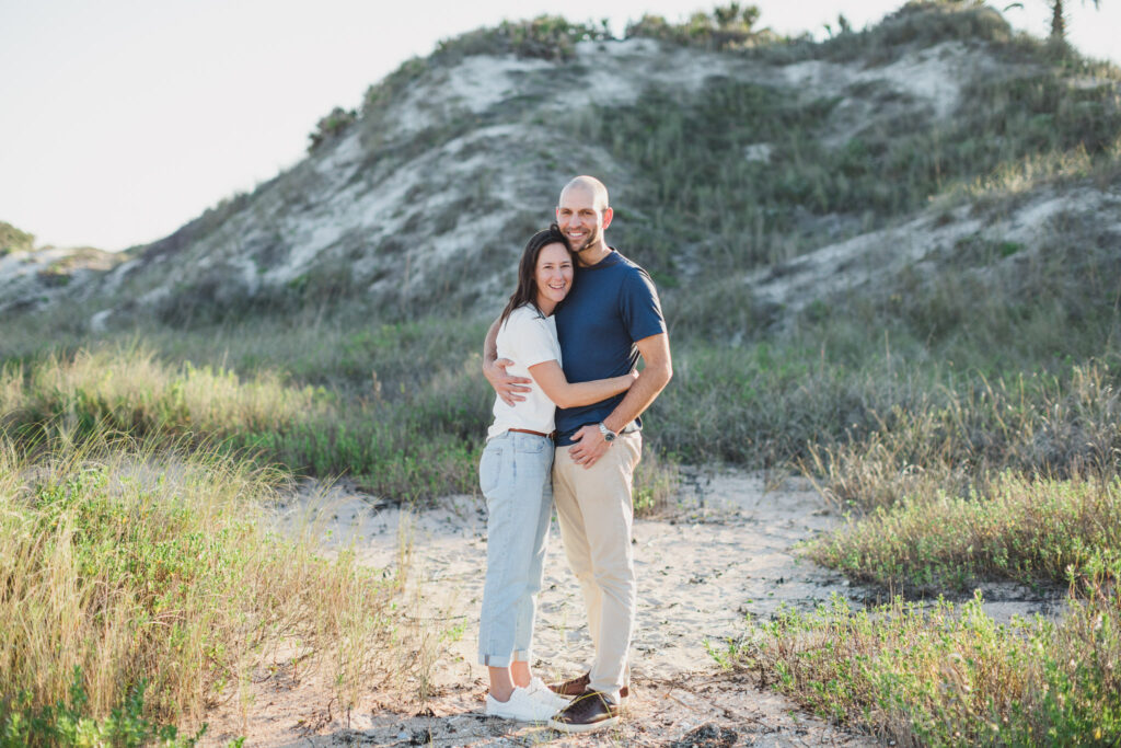 couple hugging on beach in during engagement photos in ponte vedra