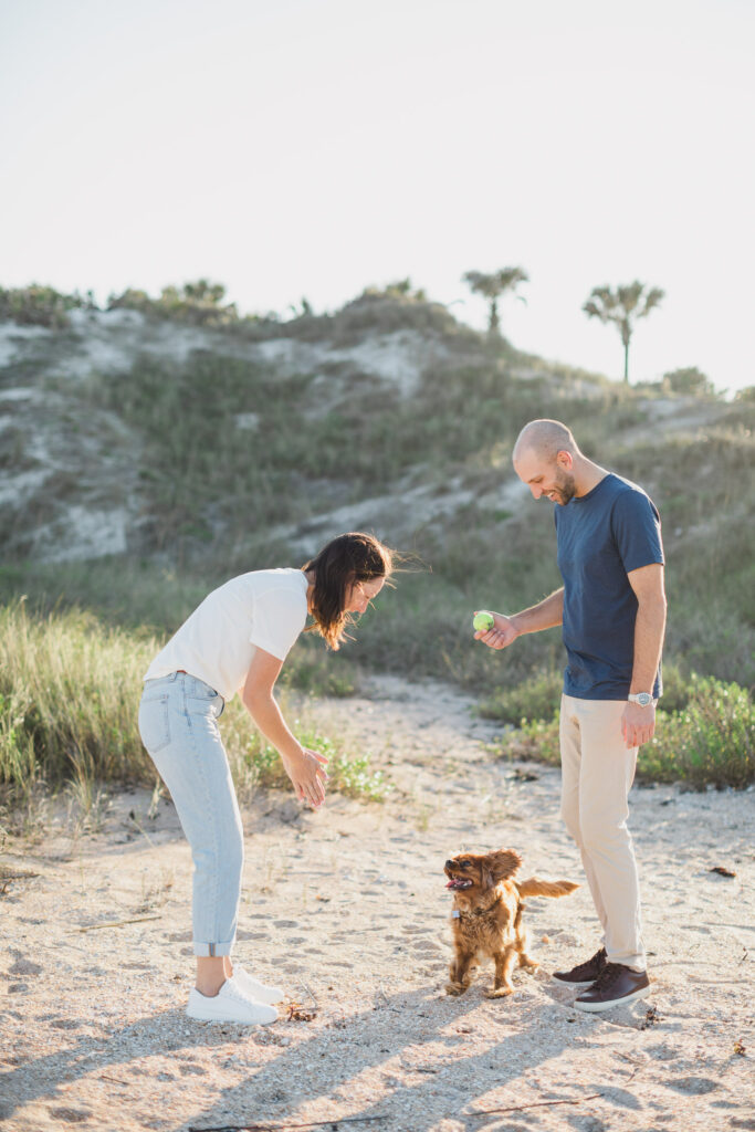 couple and their dog on the beach during engagement photos