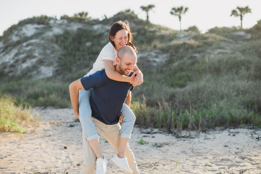 man giving woman piggy back ride during beach engagement