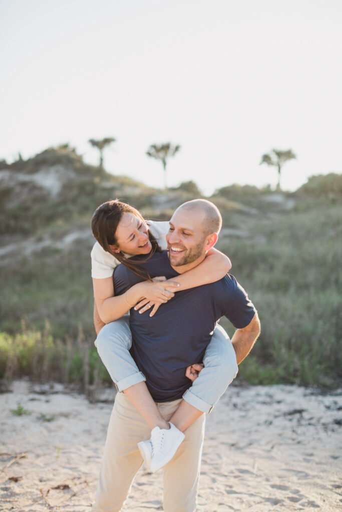 couple playing on beach during engagement session