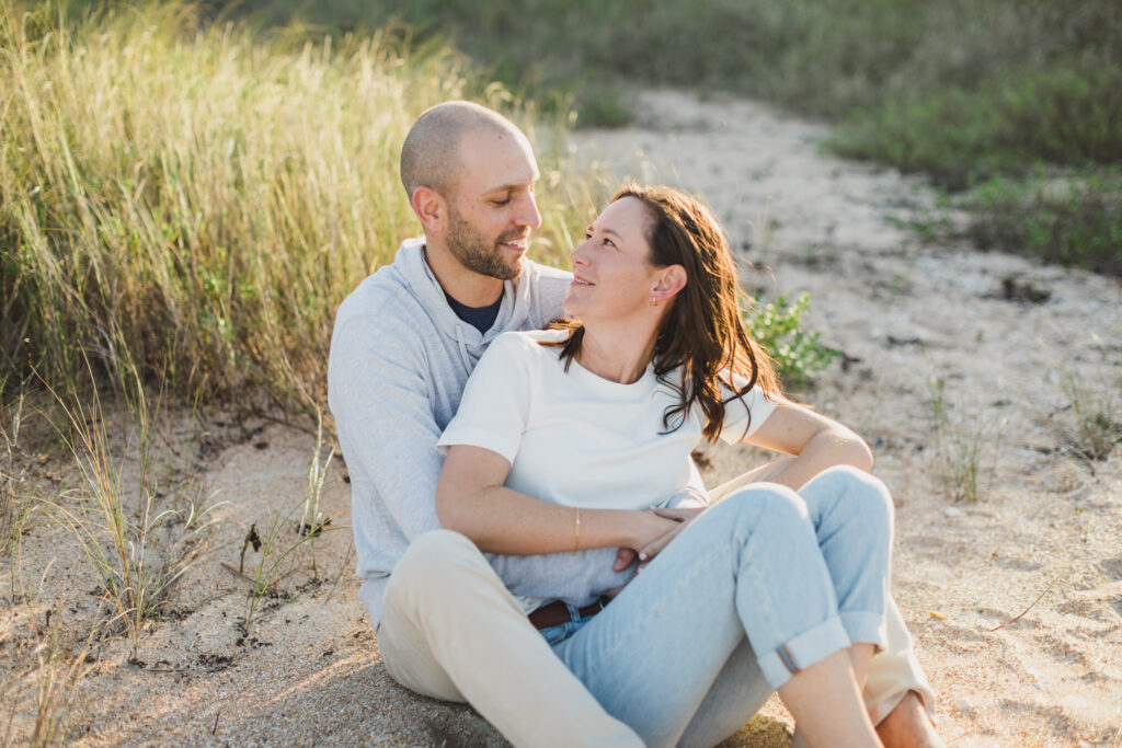 man hugging woman as they sit on the beach for engagement photos