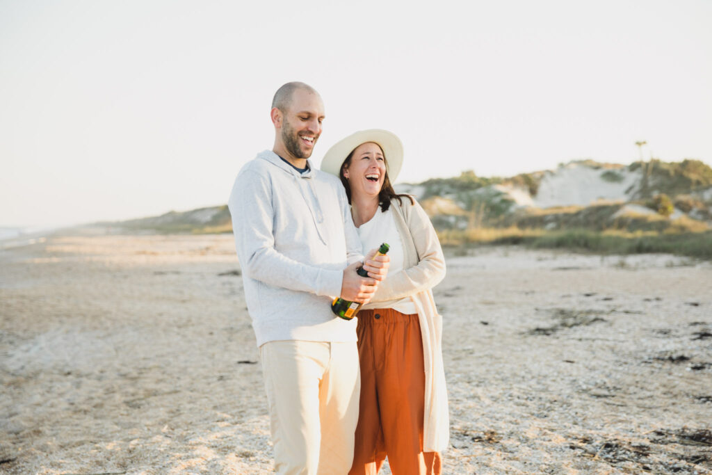 couple popping champagne on the beach during engagement photos
