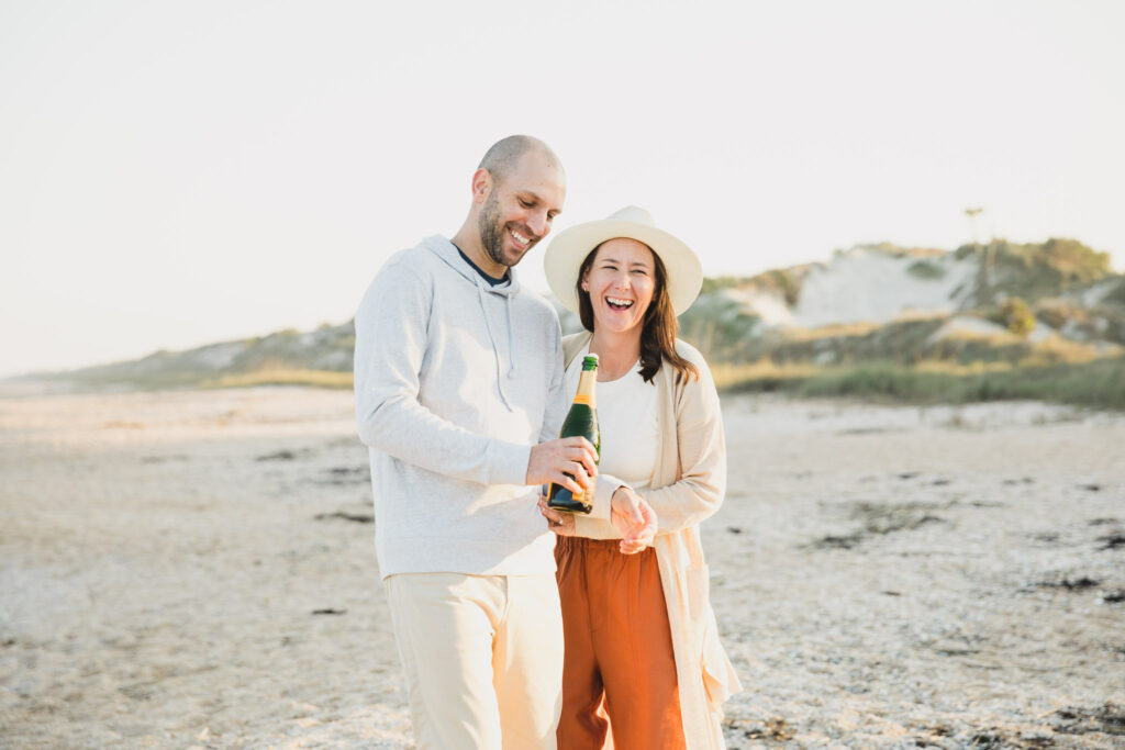 couple popping champagne on the beach
