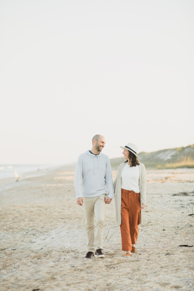 couple walking down beach during engagement photos