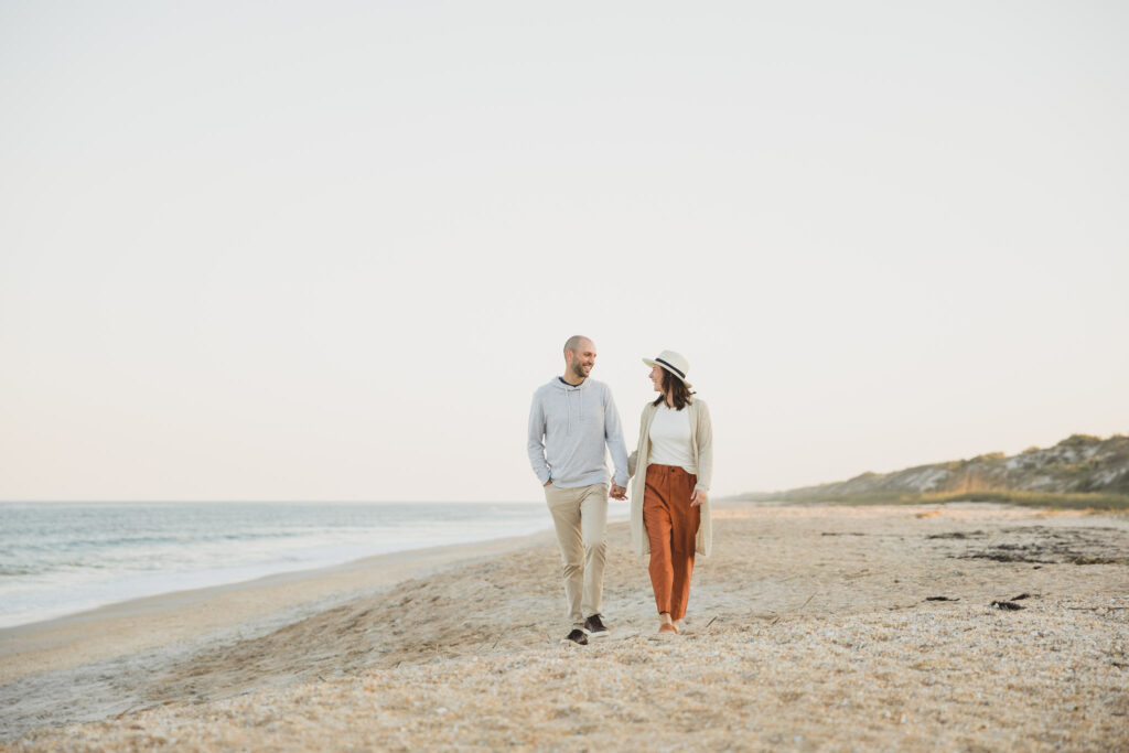 couple holding hands and walking on ponte vedra beach during engagement session