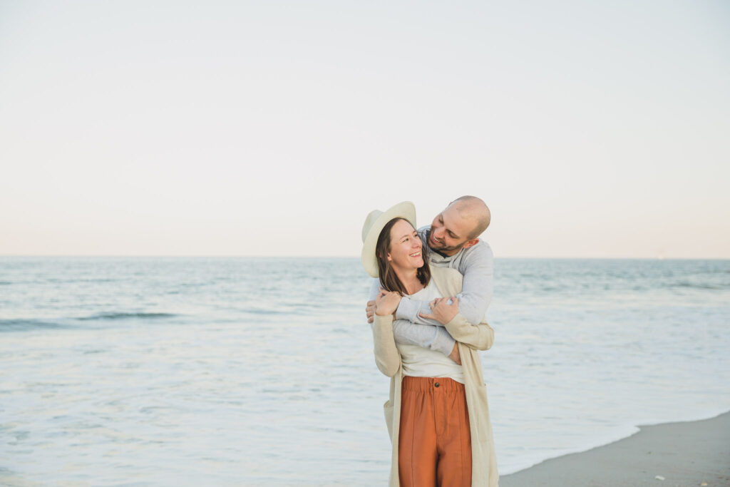 couple posing on beach for engagement session photos